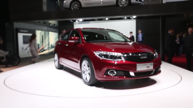 Various shots of a red Qoros 3 hatchback model rotating on a stage at the 2014 Geneva Auto Show in Palexpo Geneva Switzerland Shots of two visitors...