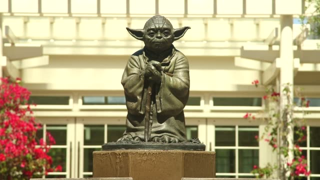 Various shots of a Yoda statue atop a fountain at the Lucasfilm Ltd campus in San Francisco California on a clear sunny day Tight tilt up shots of a...