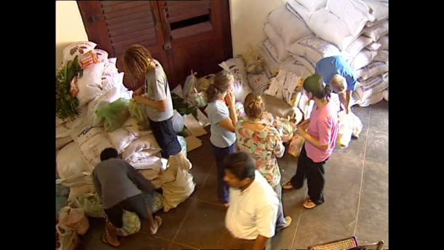 various shots of aid workers packing dry goods and fresh vegetables into bags and loading a vehicle with food and cooking equipment during tsunami... - wohltätigkeit stock-videos und b-roll-filmmaterial