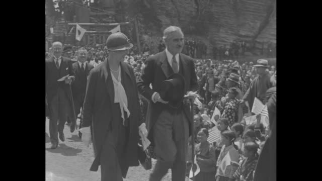 various shots of american ambassador to japan joseph grew and wife leading procession of japanese dignitaries down village street lined with crowds... - 外交点の映像素材/bロール