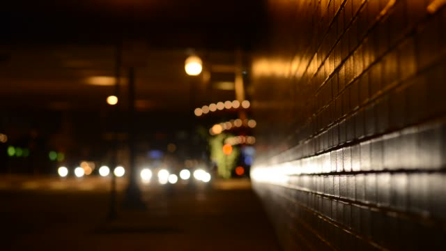 various shots of an empty street at night in downtown chicago illinois street lamp lights reflect against a brick wall as a man walks down an empty... - brick wall stock videos & royalty-free footage