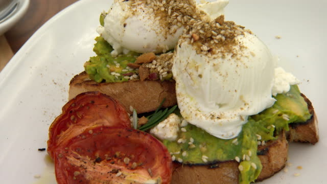 vídeos y material grabado en eventos de stock de various shots of avocado feta cheese dukkah spices and seeds garnish poached eggs and roasted tomatoes with toast - aguacate