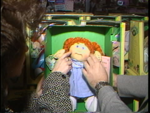 stockvideo's en b-roll-footage met various shots of cabbage patch kids dolls of different varieties sitting in their packaging at a toy store. one shot shows the adoption papers that... - pop speelgoed