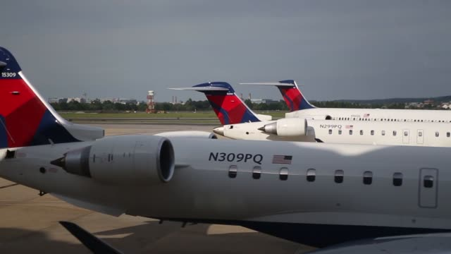 various shots of delta air lines planes at ronald reagan national airport in washington dc a wide shot of a delta airplane backing up as another... - aeroporto nazionale di washington ronald reagan video stock e b–roll