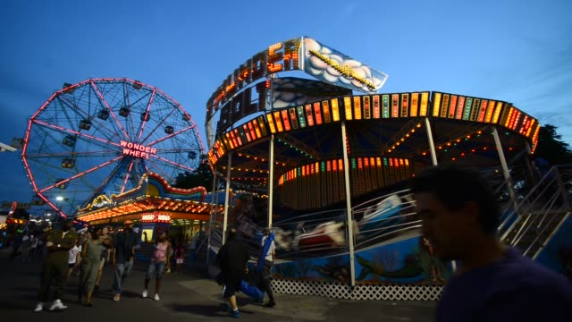 various shots of denos wonder wheel amusement park at night in coney island, new york, a wide shot of the thunder bolt ride in the foreground and the... - coney island stock videos & royalty-free footage