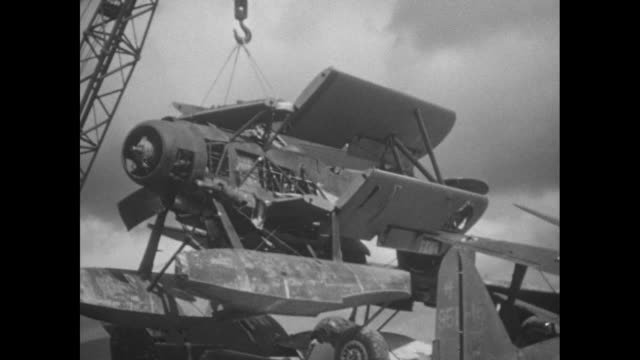 various shots of destroyed japanese military airplanes / crane lifts airplane wreckage / various shots of m4 sherman tanks using flame throwers on... - 1940~1949年点の映像素材/bロール