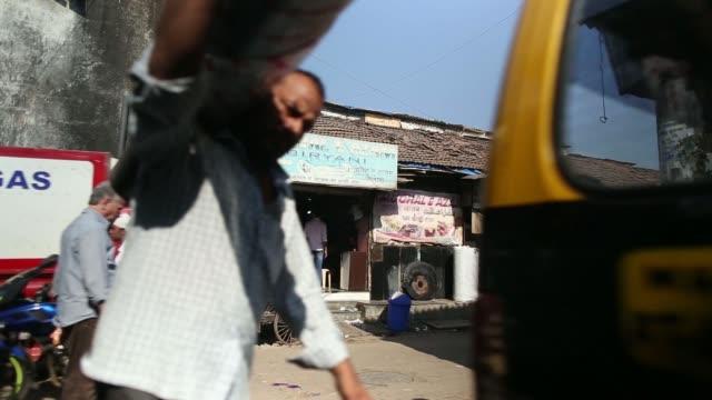 Various shots of Dharavi taxi turns into small street roadside vendors pedestrians walking past tilt up of fruit vendor selling apples grapes...