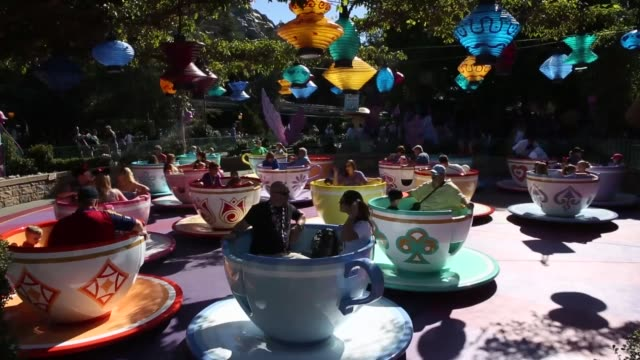 vídeos de stock e filmes b-roll de various shots of disneyland visitors riding the teacups ride people getting on and off the ride race towards different colored teacups disneyland... - chávena de chá