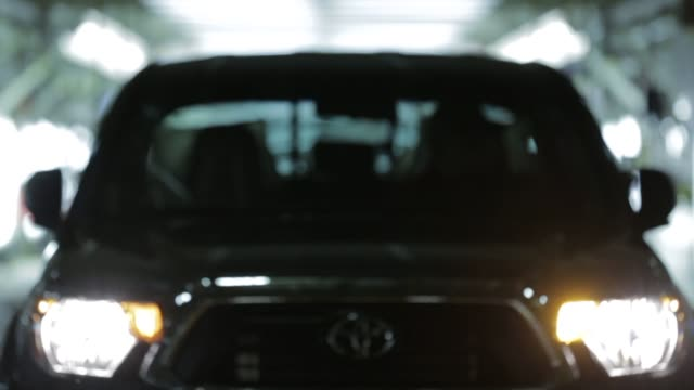 stockvideo's en b-roll-footage met various shots of finished toyota tacoma and toyota tundra model pick up trucks being driven off the assembly line at the toyota motors manufacturing... - toyota motor