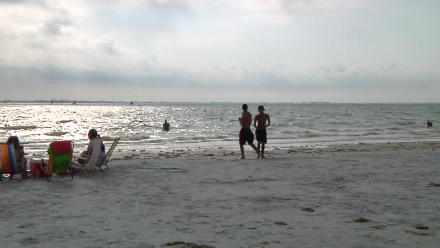 various shots of fort meyers beach on march 23 a wide panning shot of kids playing football and people relaxing on the beach a wide shot of people... - fort myers beach stock videos & royalty-free footage