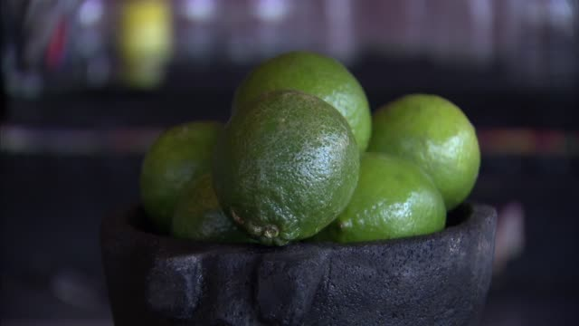 Various shots of fresh limes on display in molcajetes at a Mexican bar in Brooklyn Tight shots of fresh limes stacked in a molcajete Tight panning...