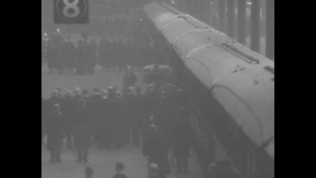 Various shots of George V's coffin arriving at Paddington Station and being loaded onto rail car / train leaves station / various shots train...