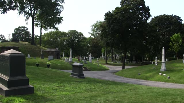 Various shots of Green Wood Cemetery in Brooklyn New York on a clear sunny day A wide panning shot of rolling hills with scattered gravestones A...