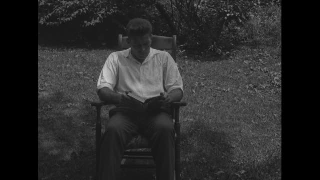 various shots of heavyweight boxer gene tunney reading book in rocking chair outdoors / tunney milks cow as man jokingly uses cow's tail like a water... - stuhl stock-videos und b-roll-filmmaterial