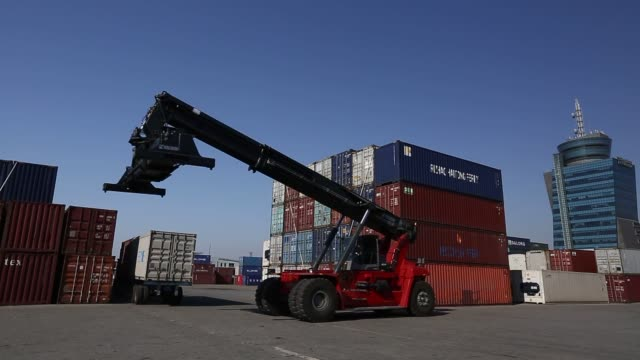 Various shots of Kalmar reachstacker loads a container onto a truck at the Port of Pyeongtaek in Pyeongtaek South Korea on Sunday March 2 A wide shot...