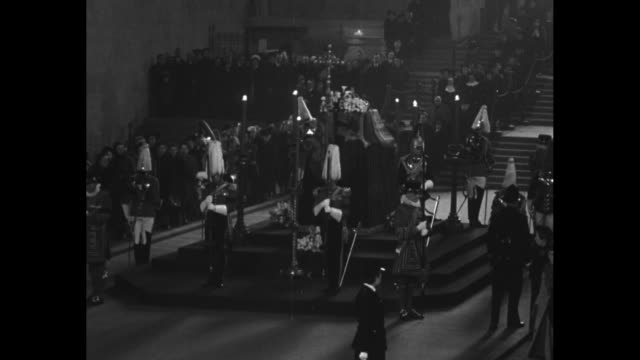 various shots of king george vi's coffin lying in state as royal guards with plumed helmets patrol perimeter of catafalque, stream of mourners seen... - 正装安置点の映像素材/bロール