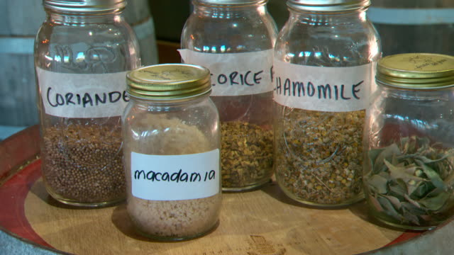 various shots of labelled jars containing seeds dried leaves and herbs including coriander licorice chamomile and crushed macadamia nuts /close ups... - cilantro stock videos and b-roll footage