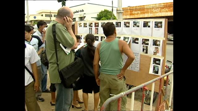 various shots of local people and toursits looking at pictures of missing people on notice boards speaking to advisors and filling out forms in a... - インド洋点の映像素材/bロール