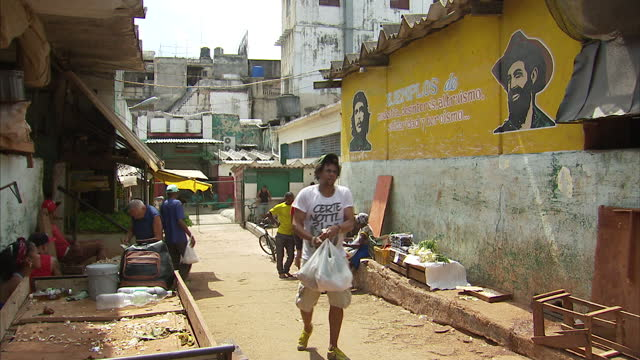 various shots of local people shopping at a market including shots of a wall mural featuring che guevara>> on march 20 2016 in havana cuba - che guevara stock videos & royalty-free footage