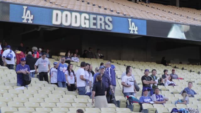 Various shots of Los Angeles Dodgers Stadium / sports fans starting to fill in seats and watch the baseball game / various views of bleachers and...