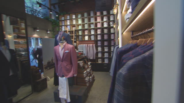 Various shots of M J Bale Gentlemen's Clothiers store as point of view walking through displays starting at entrance walking past each rack of...