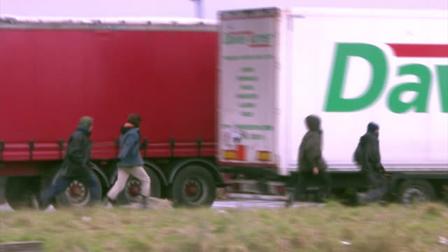 various shots of migrants in calais attempting to get into the back of ukbound lorries - back stock videos & royalty-free footage