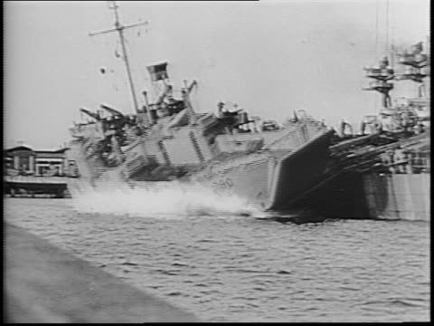 various shots of military boats collected in british harbor / man hammers at plank of wood / boat launched off side of larger vessel / man smokes... - chiatta video stock e b–roll