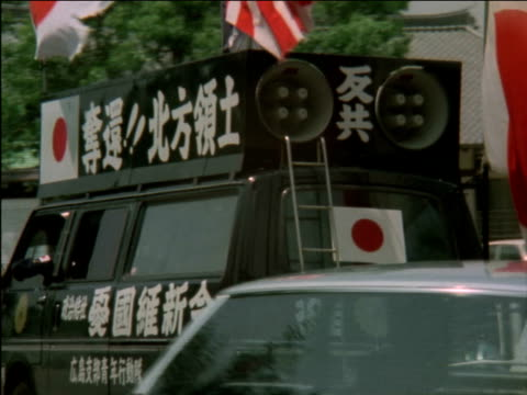 various shots of mini-vans heavily decorated with placards and flags in demonstration for peace in streets of hiroshima. protest and memorial for... - 大量破壊兵器点の映像素材/bロール
