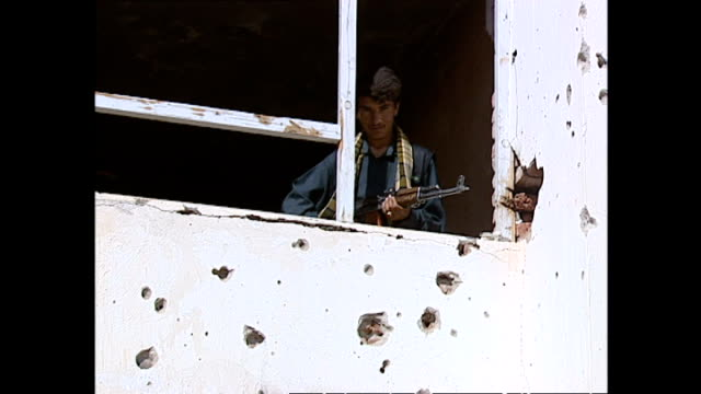various shots of northern alliance soldiers looking out from a bullet-riddled building in kapisa province. >> on october 14, 2001 in kapisa province,... - 14 15 years stock videos & royalty-free footage