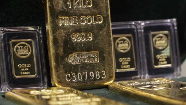 Various shots of one kilogram gold bars sit in a window display at the YLG Bullion International Co headquarters in Bangkok Thailand on Wednesday Jan...
