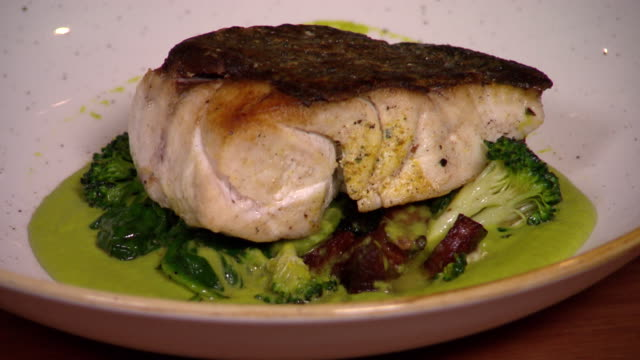 Various shots of pan fried fillet of blueeyed cod on bed of green vegetables