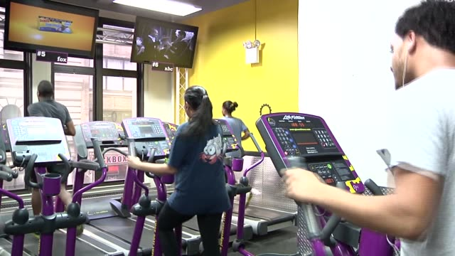 various shots of people using workout equipment at a planet fitness gym in new york city a row of people run on treadmills an african american man... - mp3 player stock videos & royalty-free footage
