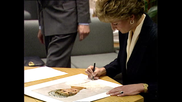 vídeos y material grabado en eventos de stock de various shots of princess diana signing a photograph of herself before departing from a king's fund presentation calling for chiropractic... - 1993