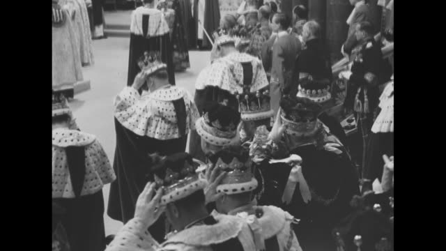 various shots of queen elizabeth ii entering main sector of westminster abbey for coronation / peers standing holding their coronets then putting... - coronation of queen elizabeth ii stock videos and b-roll footage