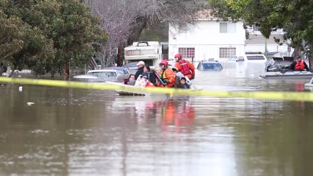 vídeos y material grabado en eventos de stock de various shots of rescuers in a boat full of people, some with pets, at a san jose neighborhood inundated by water from an overflowing creek on... - 2017