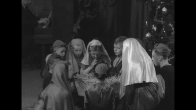various shots of schoolchildren performing nativity scene on stage, choir of schoolchildren on one side of stage singing / shot of audience / young... - キリスト降誕点の映像素材/bロール