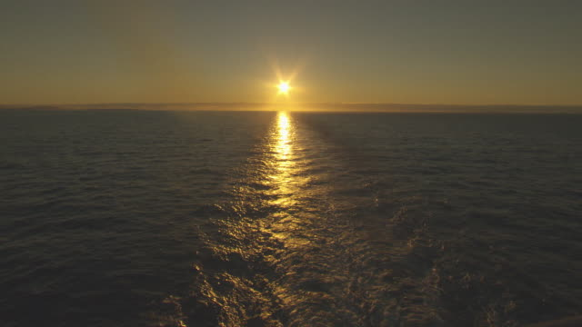 Various shots of sky and ocean at dawn silhouettes of hills and clouds on the horizon sunrise point of view of the stern of a moving ship with sun...