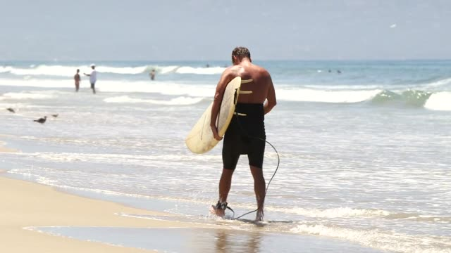 various shots of surfers in manhattan beach, california on a clear, sunny day, a medium shot of a white male surfer walking along the water with a... - wet wet wet stock videos & royalty-free footage