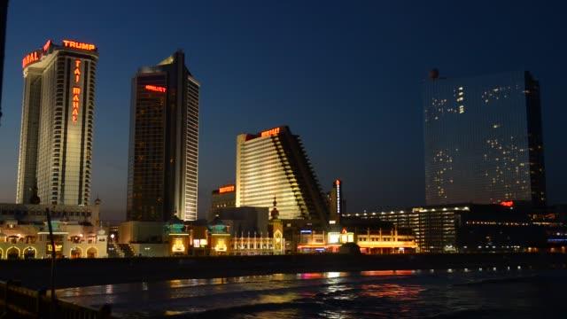 vídeos de stock, filmes e b-roll de various shots of the atlantic city boardwalk with the taj mahal revel and resorts casinos lit up at night in atlantic city new jersey a wide shot of... - atlantic city