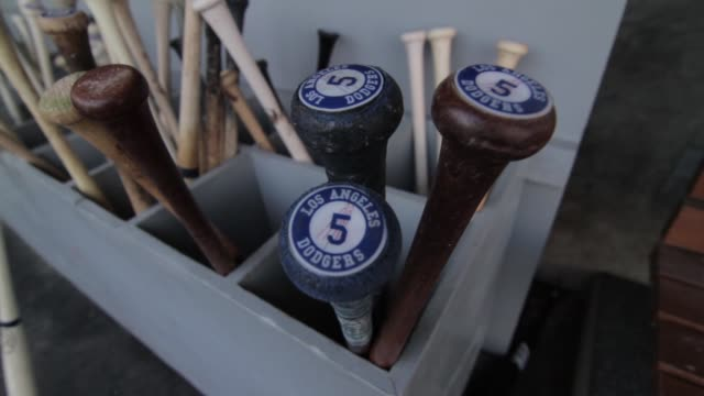 Various shots of the Los Angeles Dugout / baseball equipment / baseball helmet with Dodgers logo / Baseball bats with Dodgers logo / baseball player...