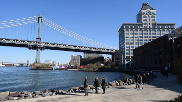 vídeos de stock e filmes b-roll de various shots of the manhattan bridge from the brooklyn, new york waterfront, various shots of the manhattan bridge between buidings in brooklyn, new... - ponte de manhattan