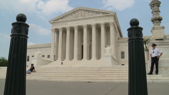 Various shots of the US Supreme Court on a summer day with a mix of sun and clouds Shots include a large flagpole flying the Stars and Stripes the...