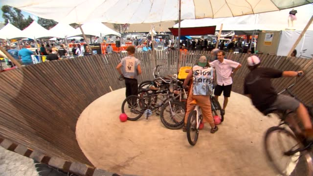 various shots of two bmx bike riders riding in a circle around the whiskeydrome structure at the bay area make faire - bmx cycling stock videos and b-roll footage