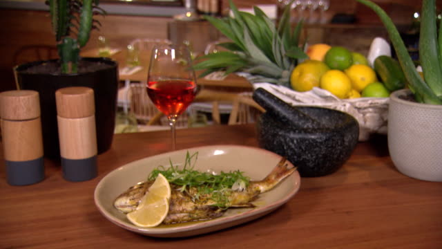 various shots of whole baked baby snapper, lemon wedge and garnish put onto dish. dish on table with salt and peper shakers, glass of rose wine,... - fruit bowl stock videos & royalty-free footage