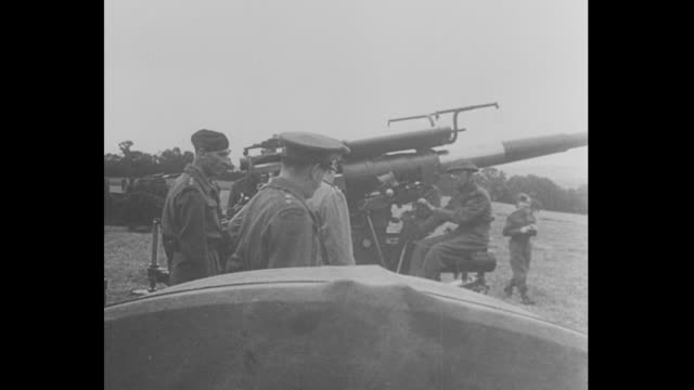 Various shots of Winston Churchill cigar in mouth and binoculars hanging around neck inspecting antiaircraft guns amid soldiers / his daughter Mary...