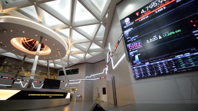 vídeos de stock, filmes e b-roll de various shots of workers and securities tickers inside the indonesia stock exchange on thursday april 10 a wide panning shot of atrium with corporate... - sinal informativo