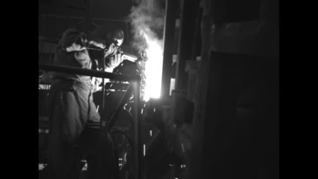 Various shots of workers using welding torches to construct landing barges / Note exact month/day not known