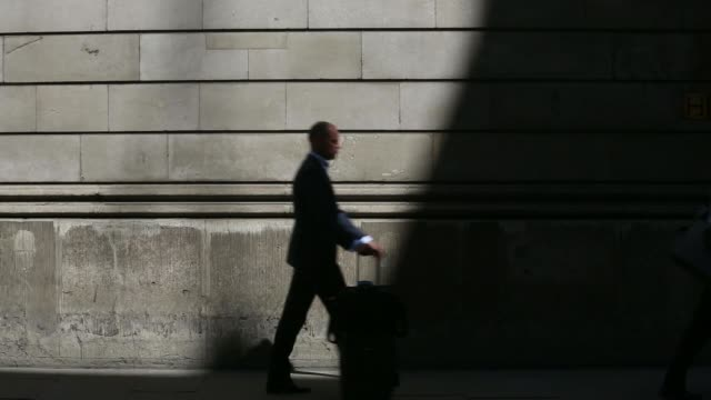 various shots pedestrians and traffic pass in and out of shadows outside the bank of england on a sunny summer day in london, uk, on friday, june 6... - 金利点の映像素材/bロール
