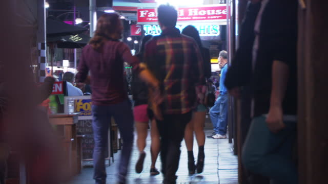 various shots pedestrians walk bustling city street at night - some anonymous - patrons sits at outdoor al fresco restaurant table / full moon over... - steeple stock videos & royalty-free footage