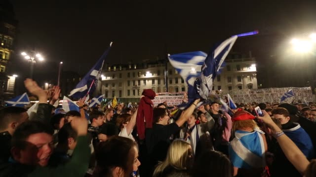 Various shots proindependence yes campaign supporters wave St Andrew's or Saltire flags the national flag of Scotland cheer and chant during a night...